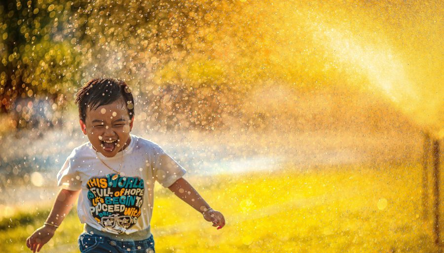 young boy running through sprinklers in daytime