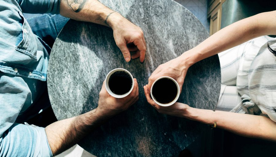 two people holding coffee cups over a round table