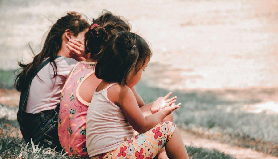 three children sitting on the ground in daytime